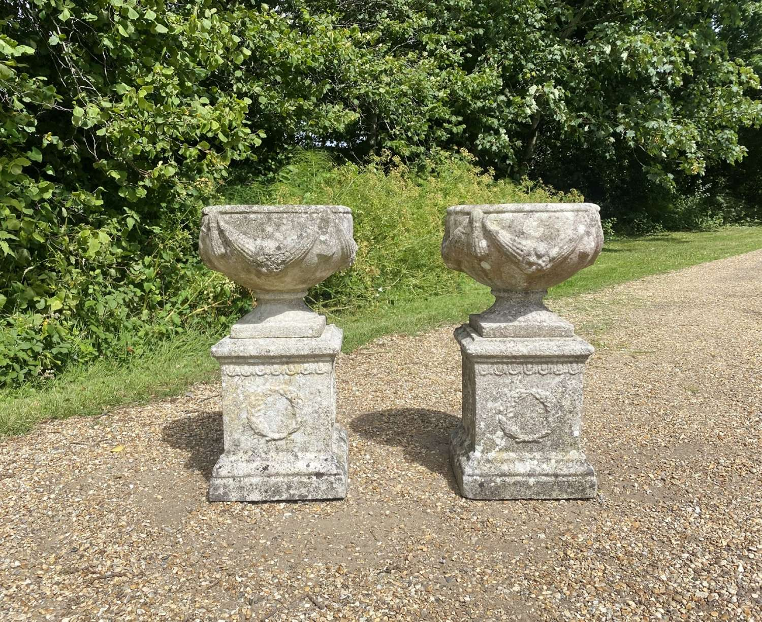 Pair of Small Patinated Urns with Pedestals